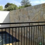 27. Pool fence and lightweight wall with stone fitted.